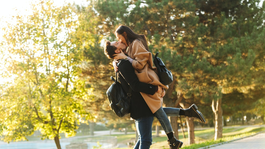 Image of a happy young beautiful loving couple posing walking outdoors in park nature kissing.