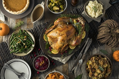 A Thanksgiving turkey is in the middle of a dinner table, surrounded by stuffing, cranberry sauce, a...