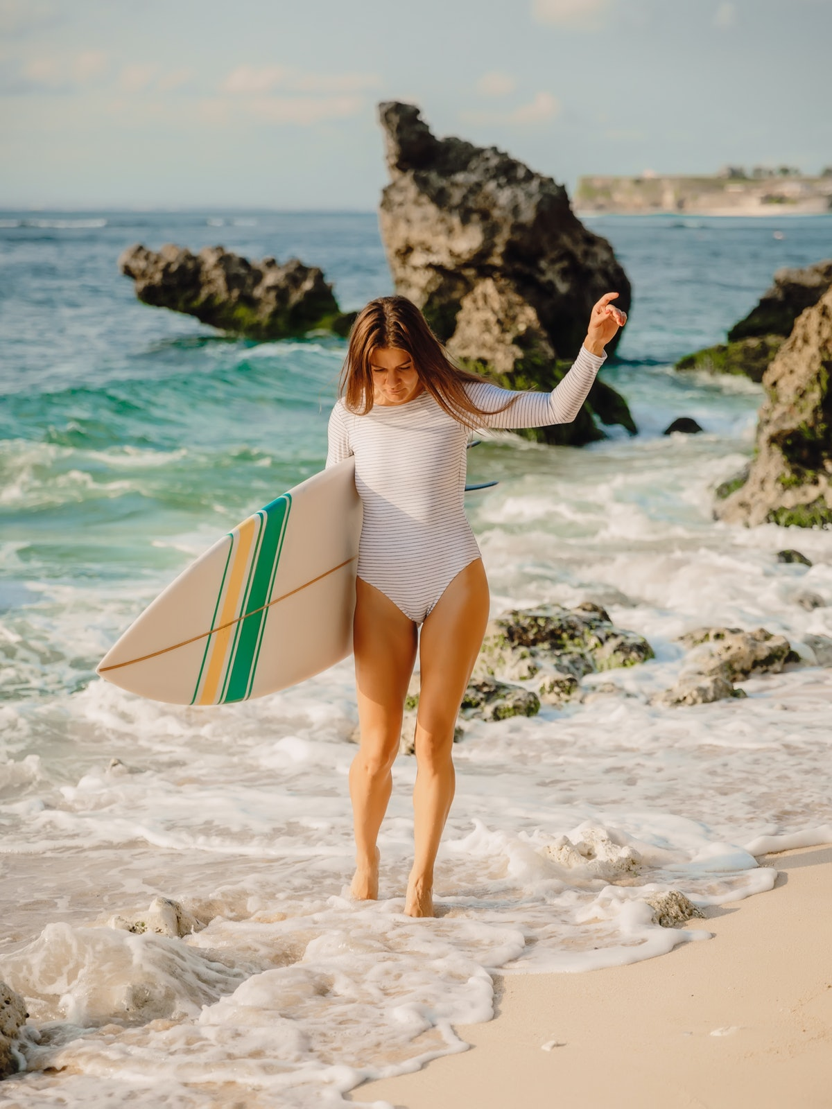 A woman in a striped one-piece bathing walks out of the ocean in Maui with her surfboard.