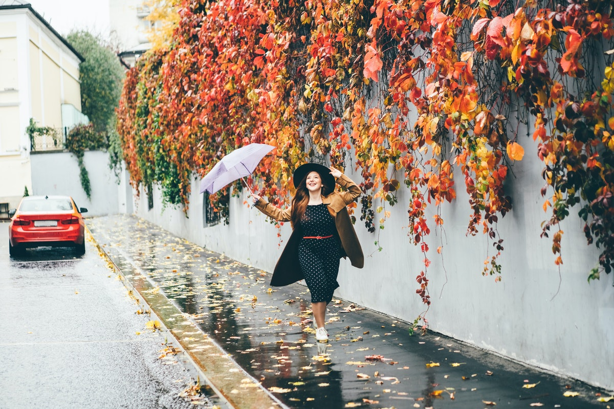 Young happy emotional girl laughing and jumping with umbrella on colored autumn street. Woman with u...