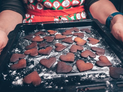 Girl holding baking tray with burnt gingerbread cookies