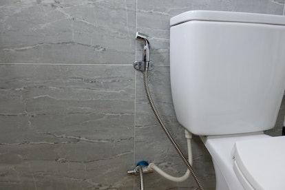silver bidet shower, bidet spray, bidet sprayer, bum gun, or health faucet beside white toilet on grey wall