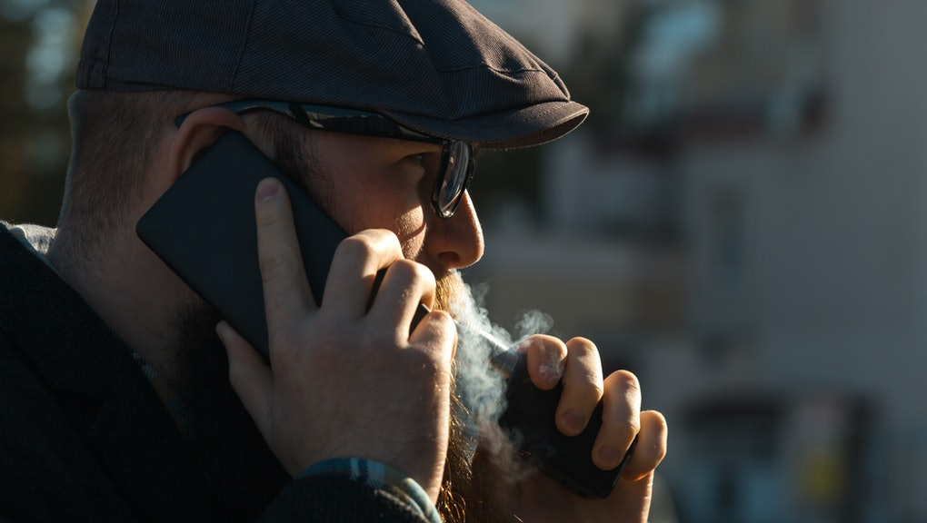 Vape bearded man in real life. Portrait of young guy with large beard in glasses and a gray cap talking on the phone and vaping an electronic cigarette on the street in the autumn.
