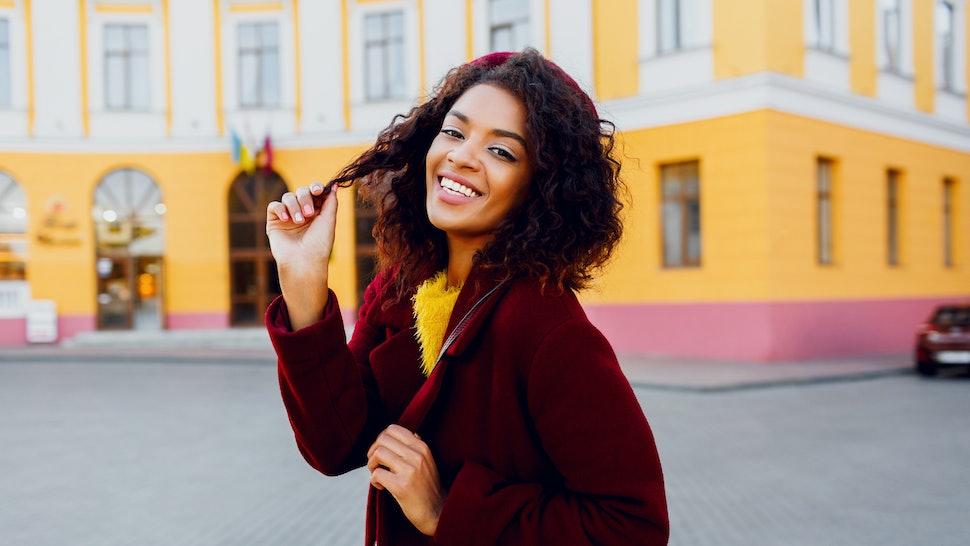 Mirthful   woman with dark skin posing outdoor. Autumn season. Wearing wool coat and cherry beret.