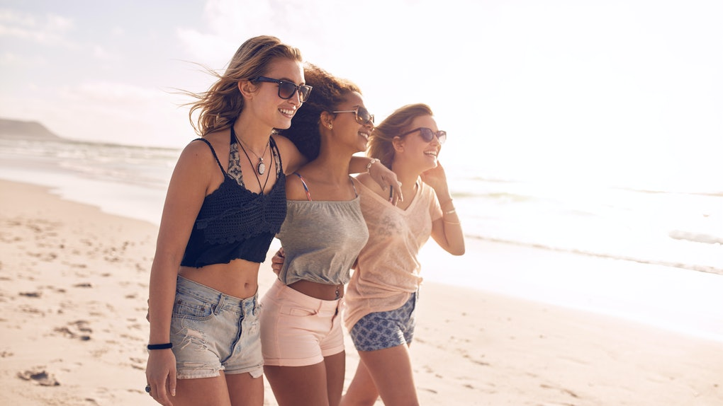 Happy young women strolling along coastline on a sunny day. Three female friends walking together on a beach, enjoying summer vacation.