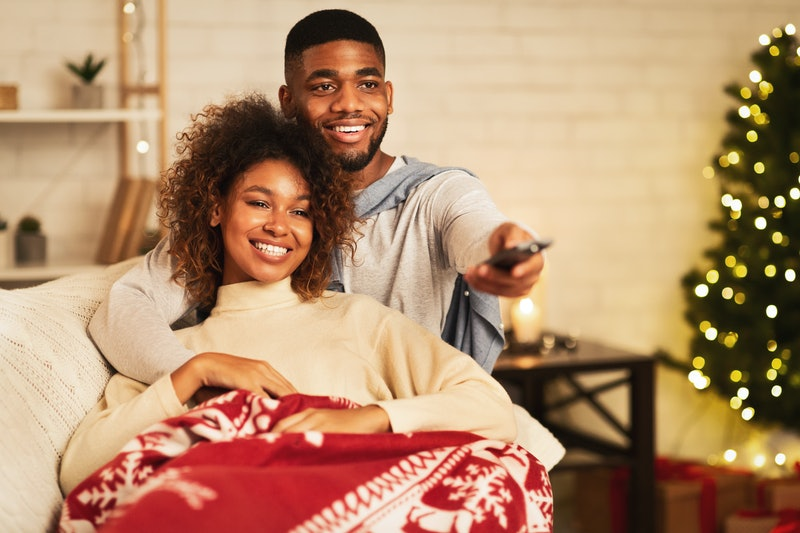 This couple cuddling under a blanket could be watching Disney+ on their Fire Stick.
