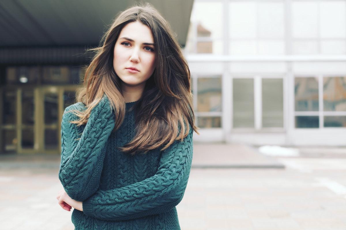 Young woman wearing woolen green sweater walking in the winter city street. Warm soft cozy image. Co...