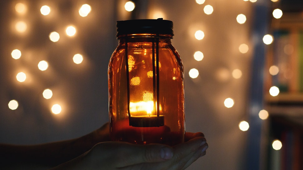 kids holds Christmas lantern in hands on lights bokeh background. New year celebration concept, festive mood