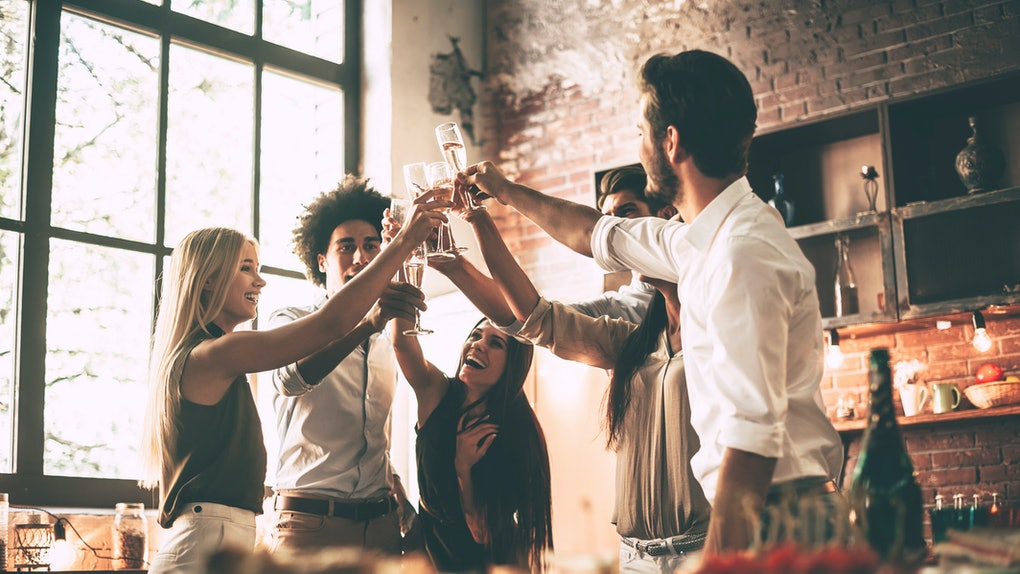 A group of friends laugh and toast their champagne flutes in a kitchen at a Friendsgiving dinner party.