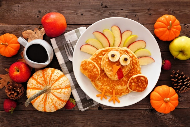 A Thanksgiving breakfast table is set with turkey-shaped pancakes, apples, pinecones, and little pumpkins.