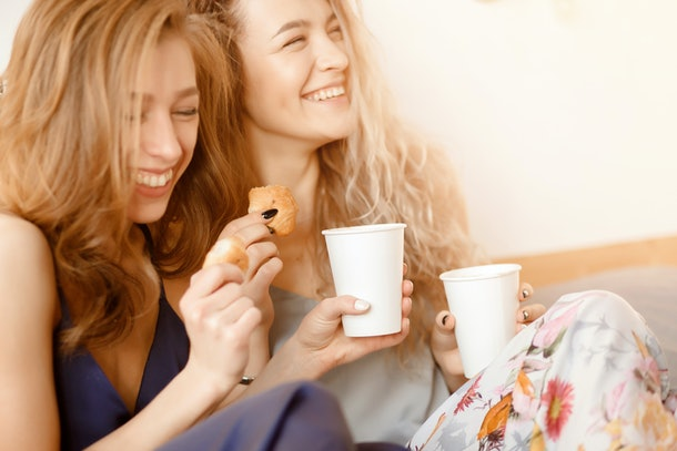 Two sisters laughing, drinking coffee, and eating Thanksgiving breakfast in bed.