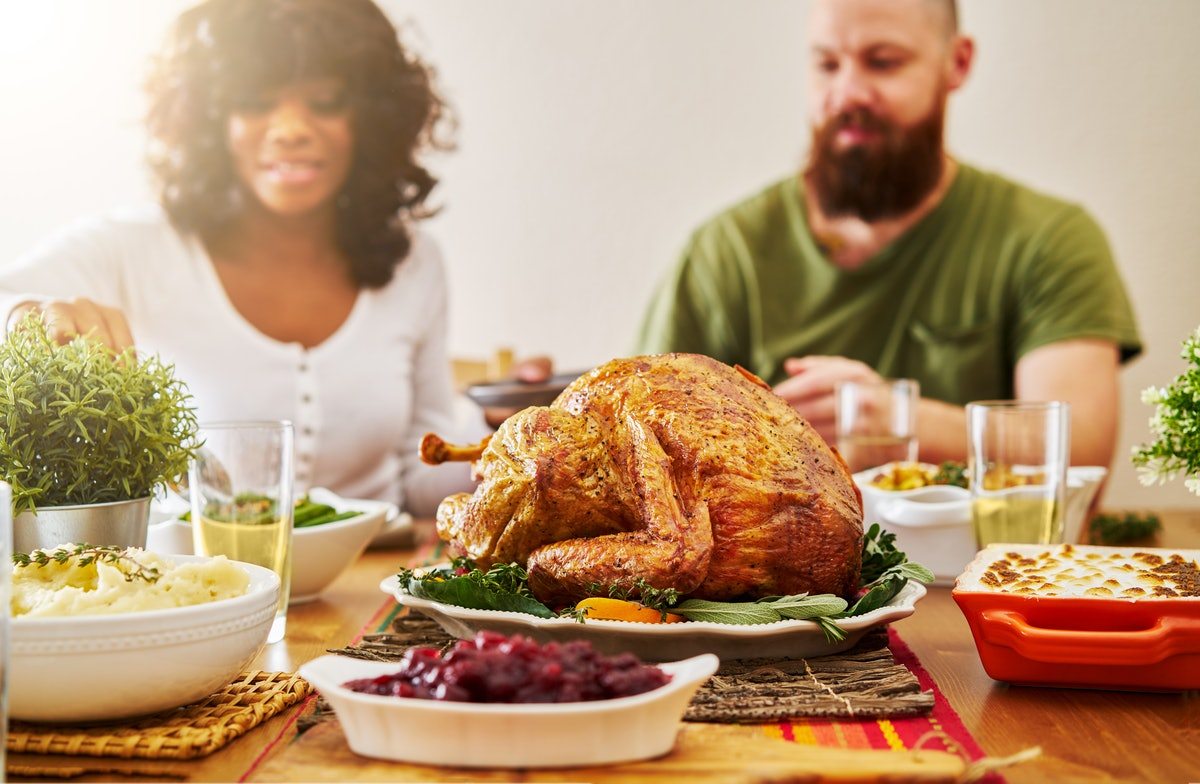 interacial couple eating thanksgiving dinner with focus on turkey