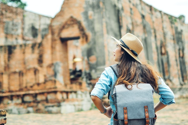 A woman wearing a blue backpack and tan straw hat with her back to the camera, explores ancient ruins in the background.