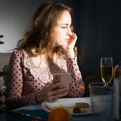 Upset woman sitting at table celebrating holiday alone and using phone at Christmas night
