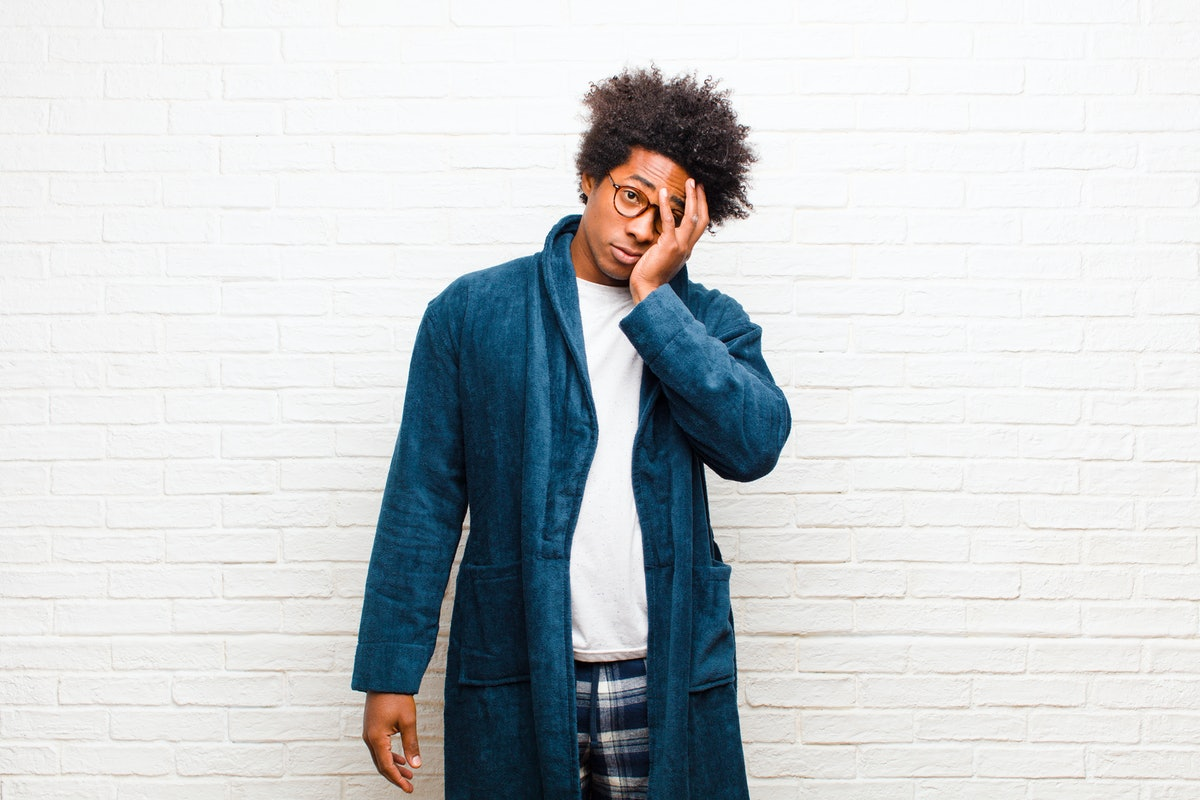 young black man wearing pajamas with gown feeling bored, frustrated and sleepy after a tiresome, dull and tedious task, holding face with hand against brick wall