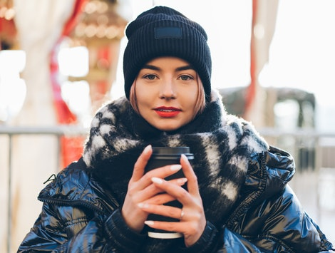 Beautiful young female with red lips wearing black winter hat and wide scarf standing by illuminated carousel with coffee to go while smiling and looking at camera