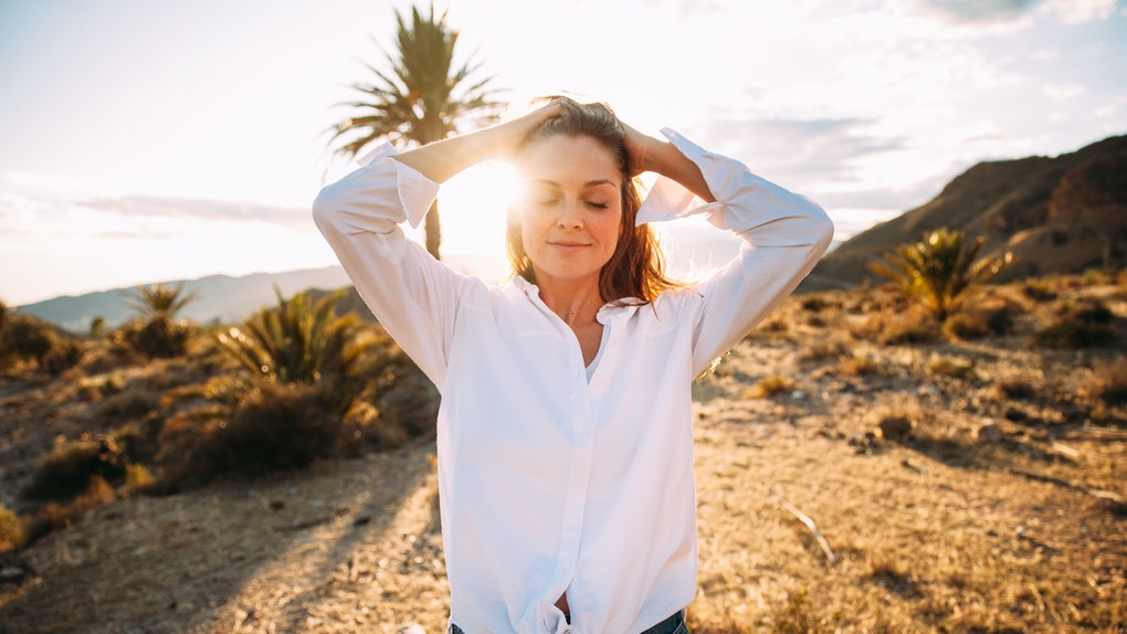 A woman in a white button-down smiles in a desert landscape with a palm tree and mountains in the background.