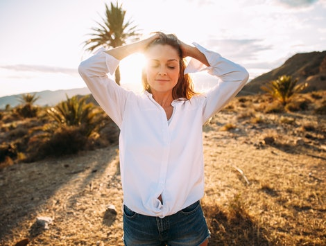 A woman in a white button-down smiles in a desert landscape with a palm tree and mountains in the ba...