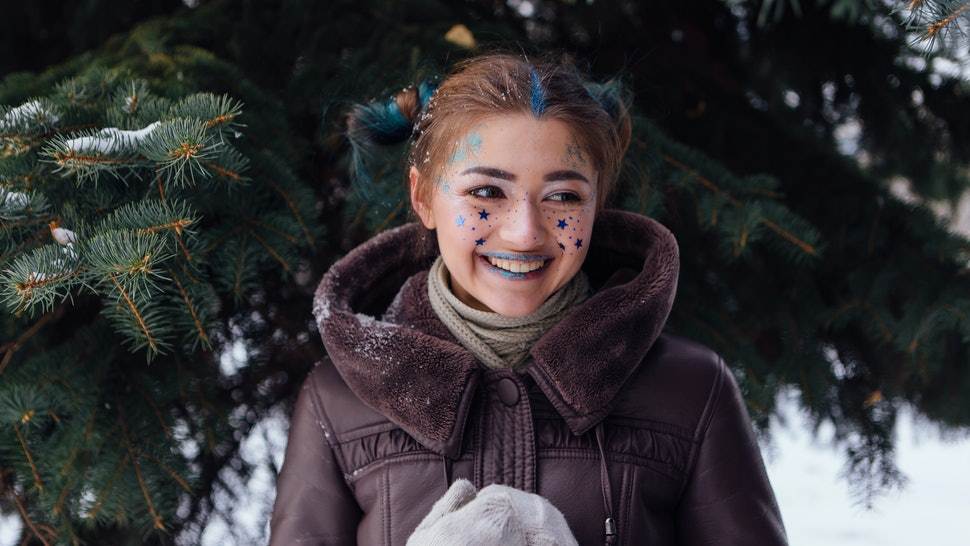 Winter portrait of a girl with bright make up and blue stars on face