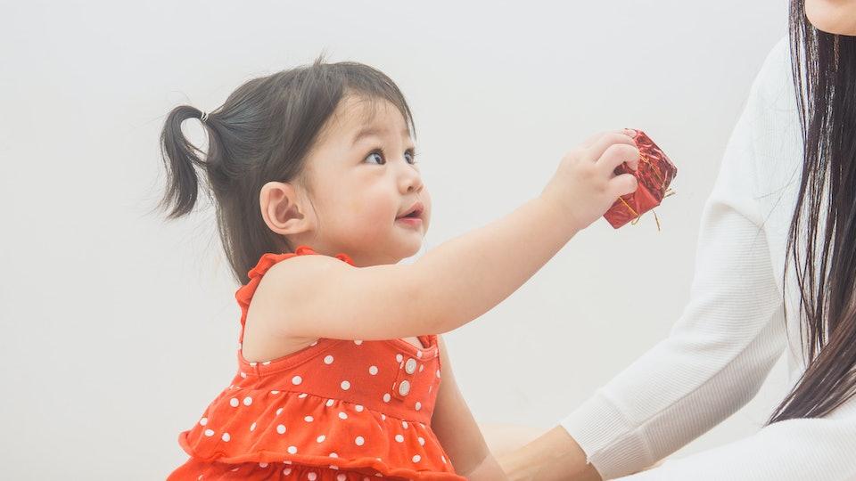 Little girl giving her mom a Christmas present