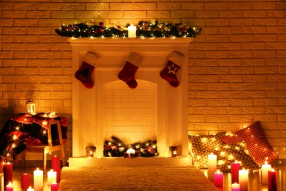 White decorated fireplace with stocking socks on brick wall background
