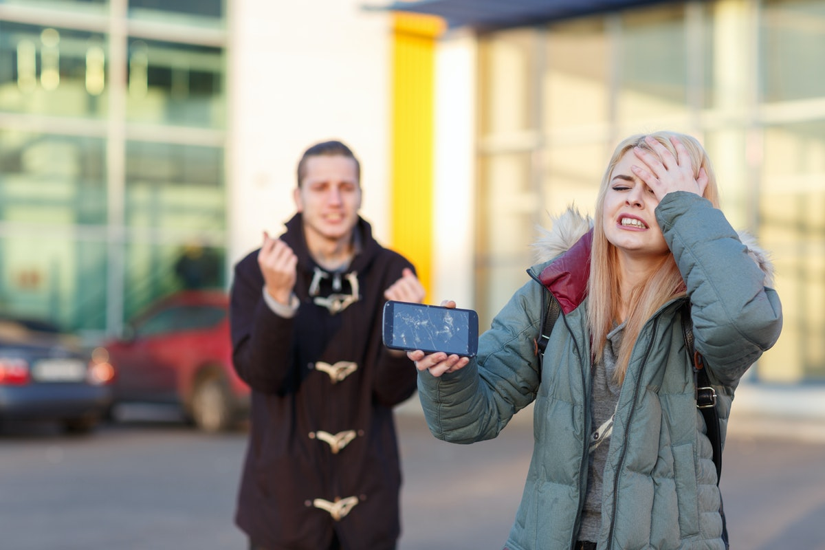 A young couple with frustrated emotions because of a broken smartphone stand on the street.