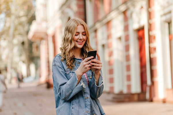 portrait of a young cute blonde with curly hair looking at iPhone and smiling