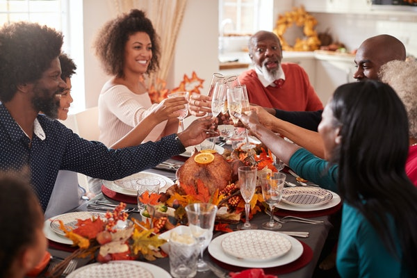 A big family raises their glasses to make a toast at their Thanksgiving dinner table.