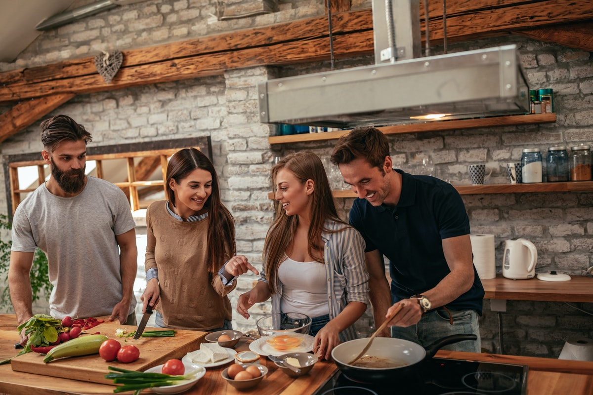 A group of friends cook and prepare a meal in the kitchen while laughing.