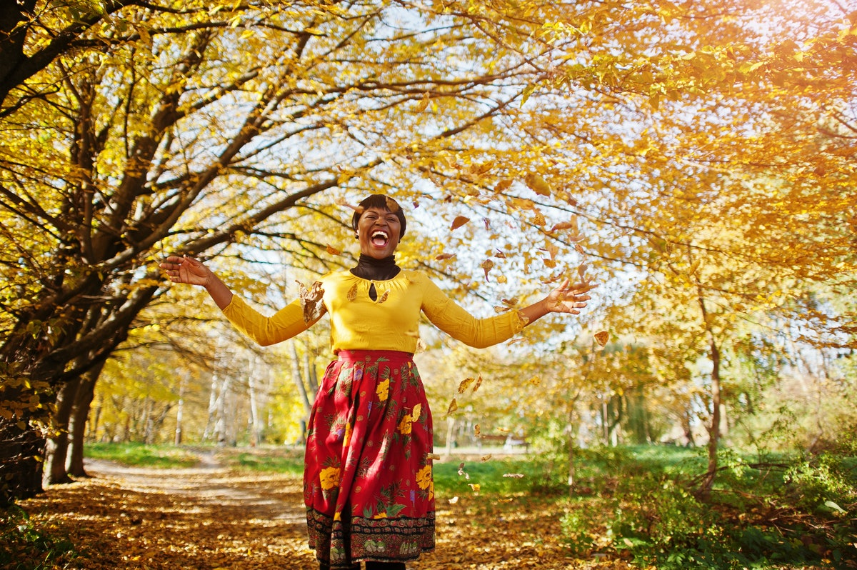 African american girl at yellow and red dress at golden autumn fall park.