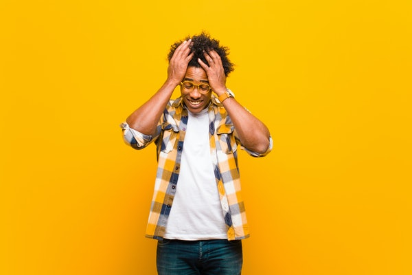 young black man feeling stressed and anxious, depressed and frustrated with a headache, raising both hands to head against orange wall