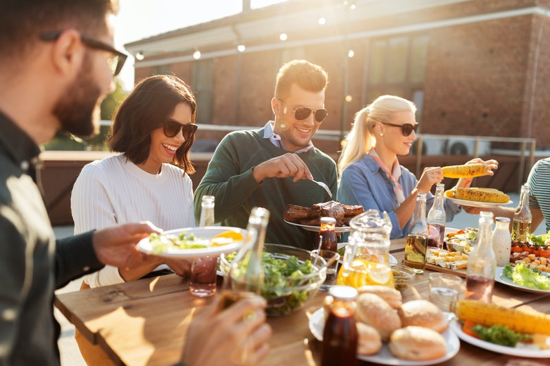 leisure and people concept - happy friends eating and drinking at barbecue party on rooftop in summer