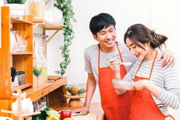 Young Asian lovely couple cooking together at home kitchen, wear red apron making lunch meal. Girl taste soup using spoon. Married people lifestyle, love relationship, or modern domestic life concept