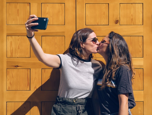 Portrait of a smiling lesbian young couple kissing and posing for a selfie in a yellow door. Happiness and joyful lifestyle concept, same sex relationship concept.