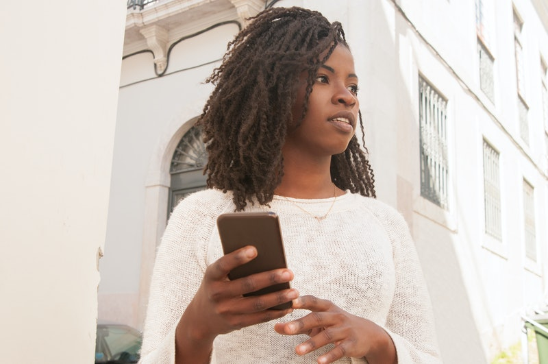 Pensive African girl with smartphone walking outdoors. Bottom view of young black woman in casual holding mobile phone and looking away. Communication concept