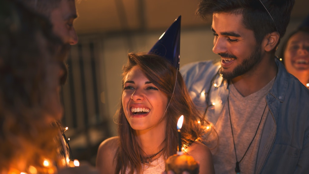 A group of friends celebrate a birthday on a rooftop, covered in lights, while the birthday girl holds a cupcake.