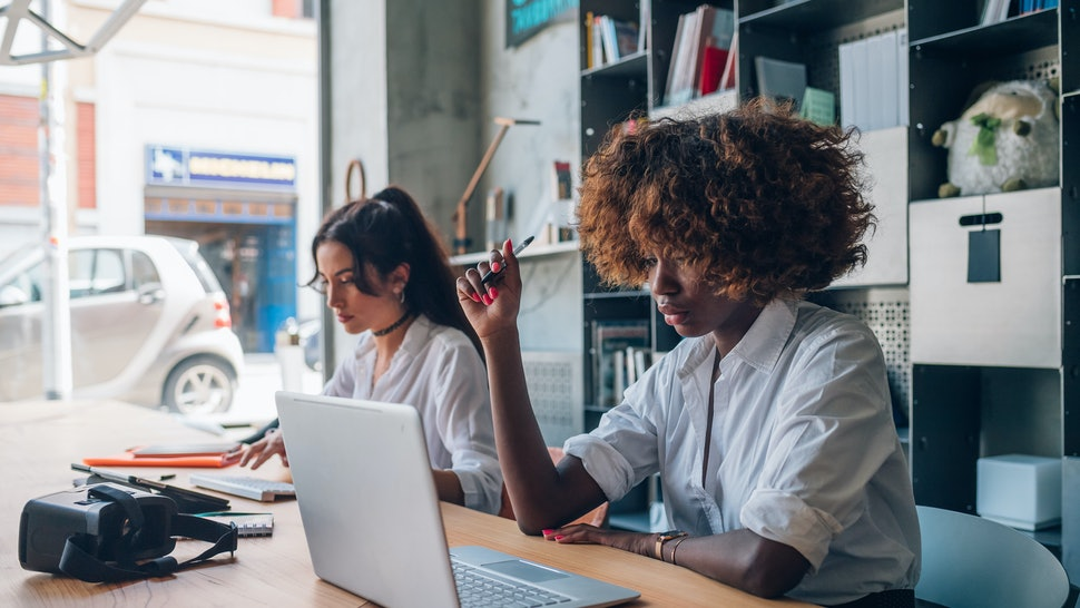two young multiracial women writing and working with digital device in modern coworking space – freelance, interaction, concentration