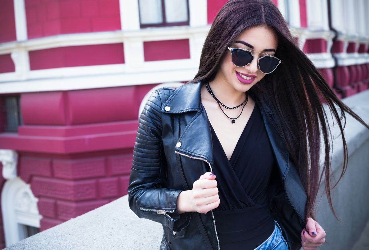 Outdoor lifestyle fashion portrait of young stylish hipster woman walking on street,wearing cute tre...