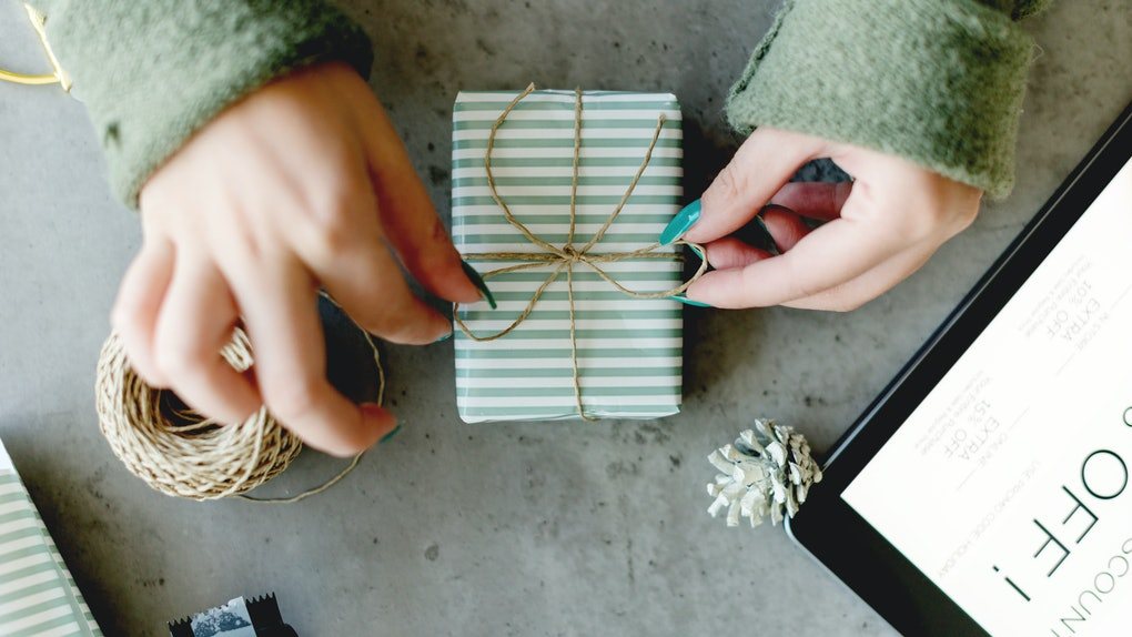 A woman ties a string bow on an engagement gift for her friend wrapped in green and white striped paper.