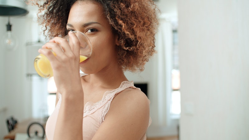 Happy mixed race woman holding orange juice and looking to camera.