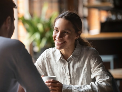 Smiling young woman talking to male friend boyfriend at meeting or romantic date in cafe, happy pretty millennial girl having conversation flirting with man sit at restaurant table drinking coffee