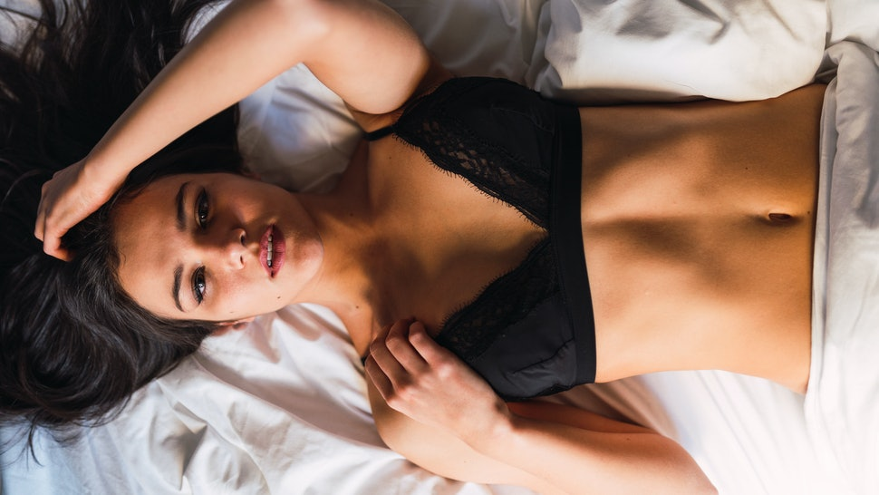 From above lovely passionate slim lady lying on bed and looking at camera in bedroom