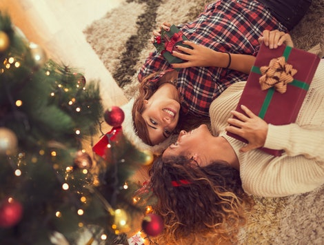 High angle view of two beautiful women lying on a carpet on a living room floor, holding nicely wrapped Christmas present boxes and exchanging Christmas gifts