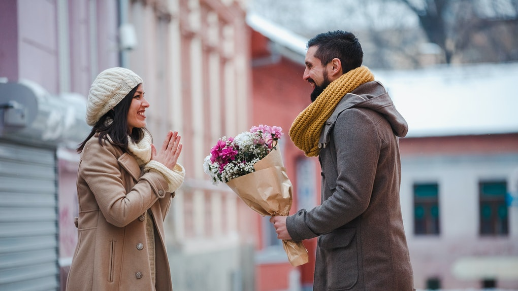 A man proposes to his girlfriend with flowers on a winter getaway.