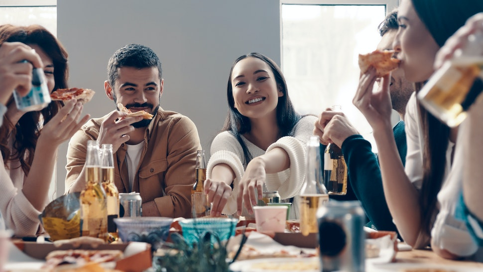 More laugh with friends. Group of young people in casual wear eating pizza and smiling while having a dinner party indoors