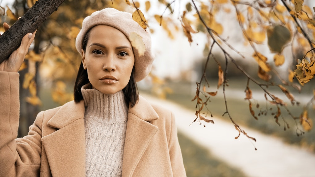 A woman dressed in a beige coat, knit sweater, and beret is surrounded autumn leaves.