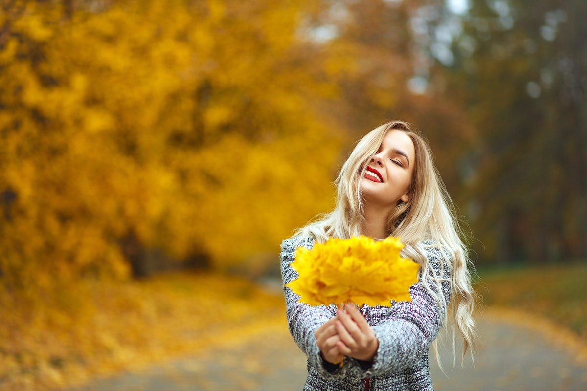 A blonde girl with red lipstick smiles, wearing a knit coat and holding a bundle of yellow leaves.