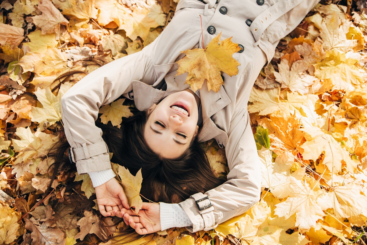 A brunette woman wearing a buttoned coat smiling lays out on top of yellow leaves.