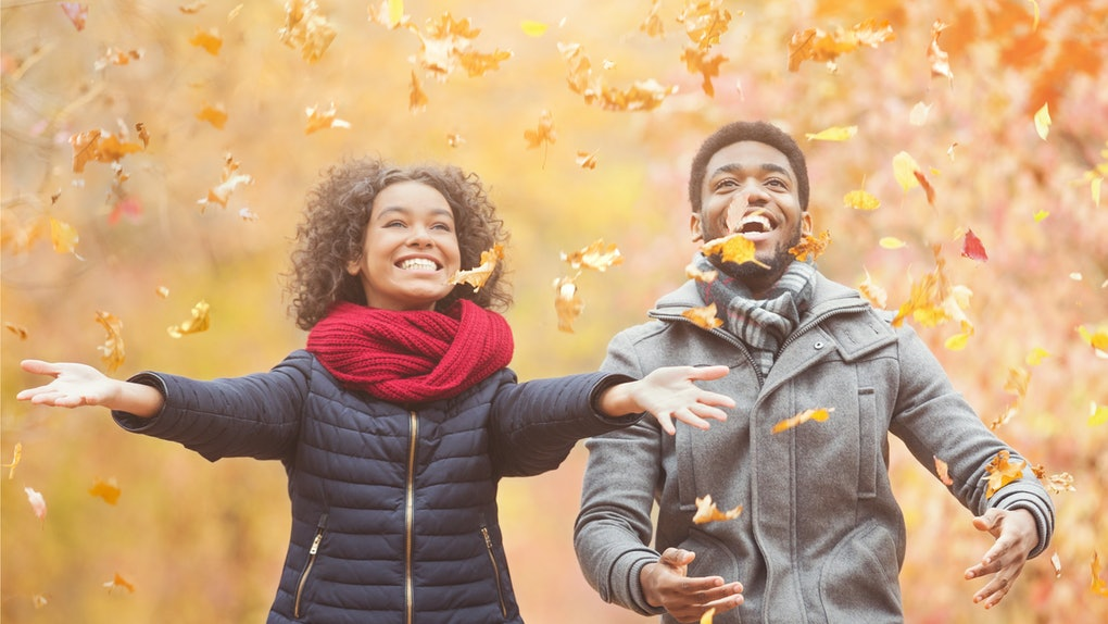 Happy afro couple throwing autumn fall leaves, walking and having fun in park