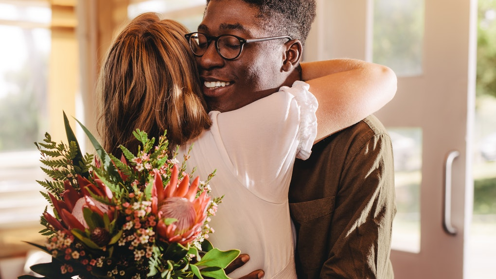 Young african man hugging his girlfriend standing in cafe. Young guy expressing his love for his lady giving flowers and a warm hug during a coffee shop date.